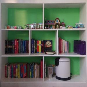 White bookshelf, seven shelves, green back, with books and Lego