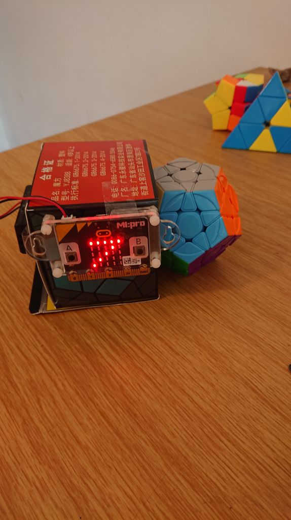 Megaminx next to box on with micro:bit counting down taped on